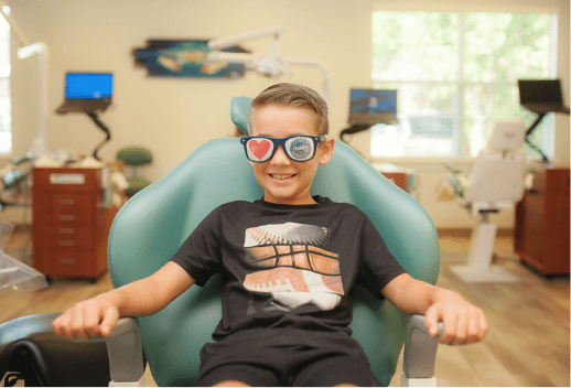 Photo of young patient smiling in a dental chair wearing sunglasses with a heart and Henry Orthodontics logo